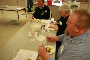 Judges Shawn O'Donnell, Tana Baumler, and Kay Nelson (left to right respectively) sample a dish. The adjudicators had significant difficulty when determining winners due to the excellence of all the dishes.
