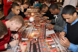 Members of the Hawks men's basketball team autograph the poster commemorating their 4th place finish in state this year.
