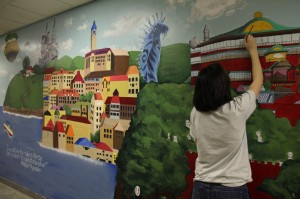 Serafina Urrutia | Hawkeye Senior Kyra Dahlman works on a mural that adorns the walls of the art hallway.
